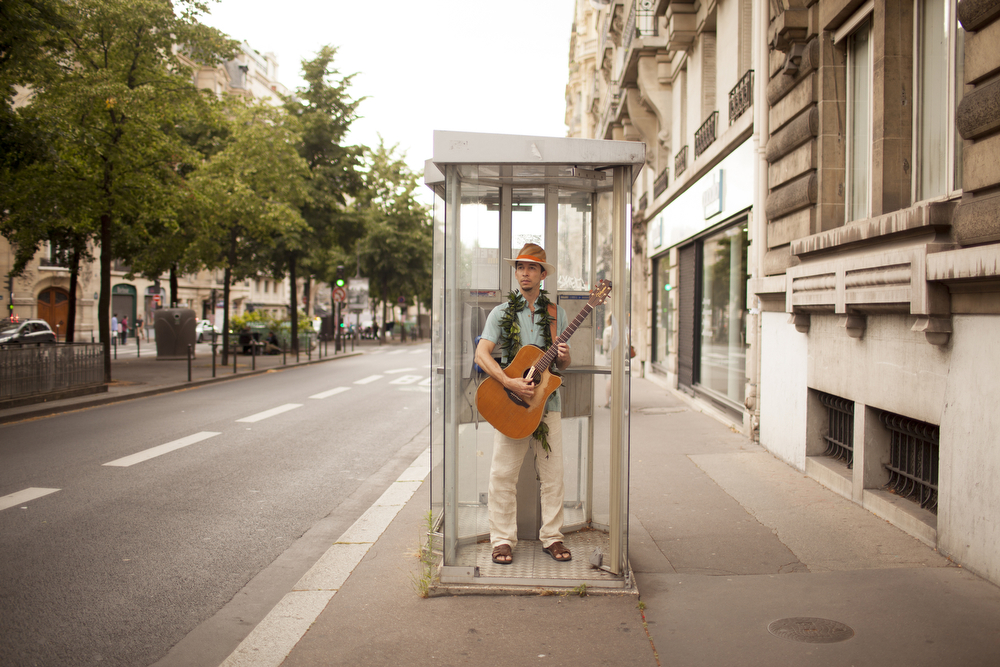 A musician in the Festival des Arts d'Hawai'i in a telephone booth