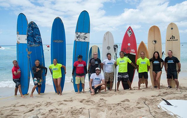 surfers standing in front their surfboards in the sand