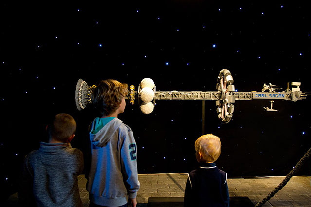 kids looking at lego space model