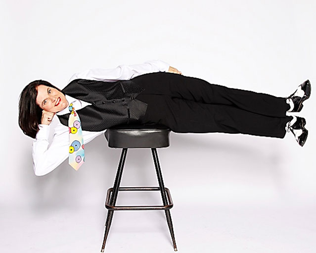 paula poundstone stretched across a chair