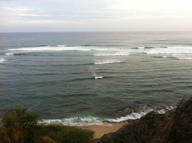 Surfers near Diamond Head cliffs